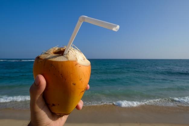 Homme tenant une noix de coco sur la plage