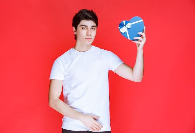 Homme tenant et offrant une boîte cadeau bleue en forme de coeur.