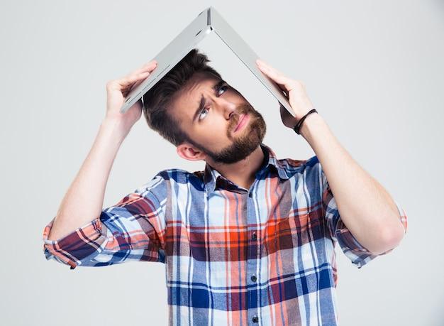 Homme tenant un ordinateur portable sur sa tête comme toit de maison