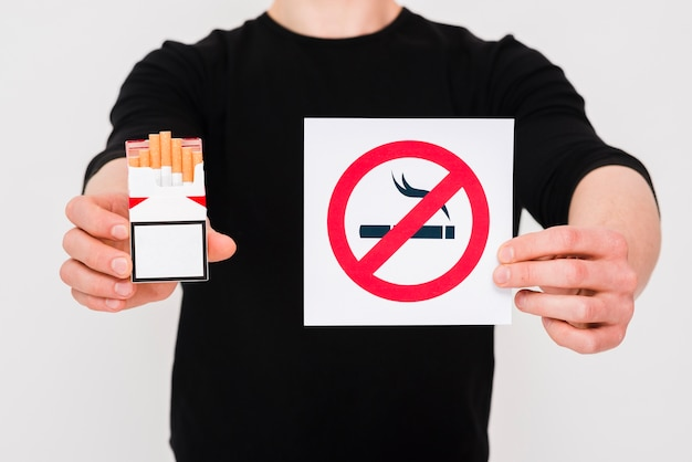 Homme tenant un paquet de cigarettes et signe non fumeur sur fond blanc