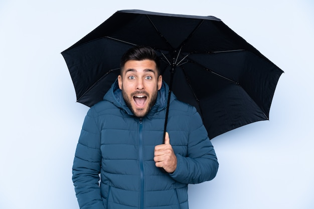 Homme tenant un parapluie sur un mur isolé avec surprise et expression faciale choquée