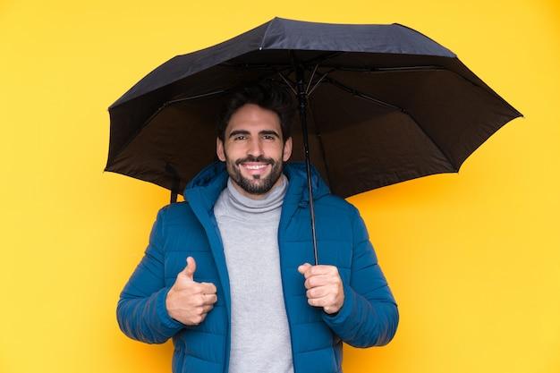 Homme tenant un parapluie sur un mur jaune isolé avec les pouces vers le haut parce que quelque chose de bien s'est produit