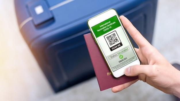 Homme tenant un passeport et un smartphone avec certificat de vaccination international code qr covid-19, valise