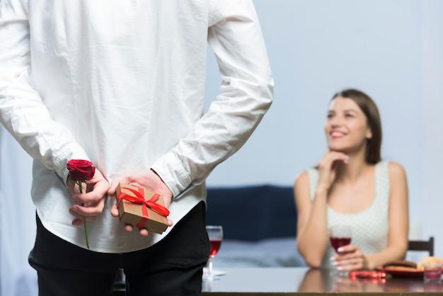Homme tenant un petit cadeau et rose derrière le dos