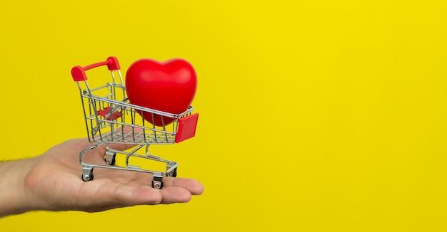 Homme tenant un petit chariot avec coeur rouge sur fond jaune.