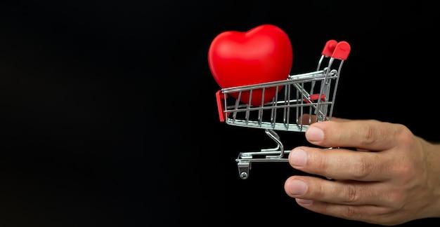 Homme tenant un petit chariot avec coeur rouge sur fond noir. concept de vente de la saint-valentin