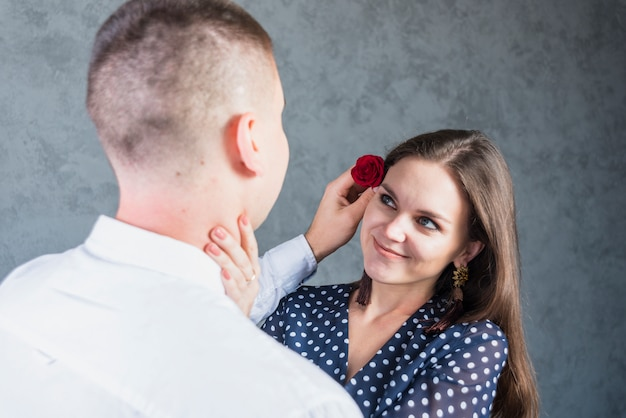 Homme tenant une petite rose à la tête de la femme