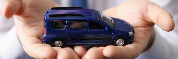 Homme tenant une petite voiture bleue dans ses mains en gros plan