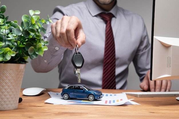 Un homme tenant une petite voiture et des clés dans ses mains.