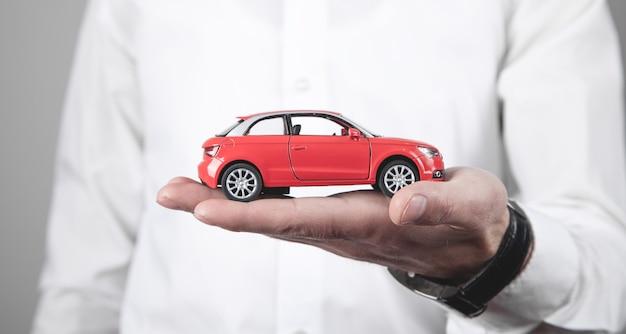 Homme tenant une petite voiture rouge.