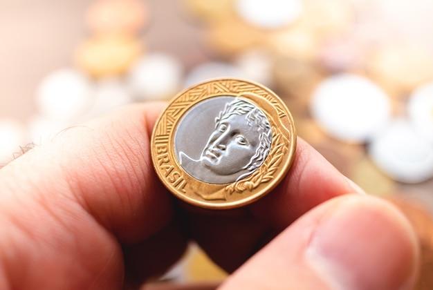 Un homme tenant une pièce de monnaie brésilienne en photo en gros plan