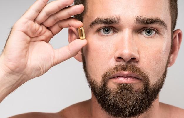 Homme tenant une pilule à côté de son visage