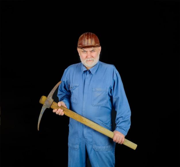 Homme tenant une pioche travailleur mineur en combinaison avec des travaux de construction et de construction de pioche