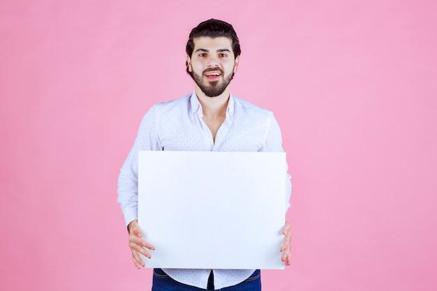 Homme tenant une planche carrée vierge devant lui.