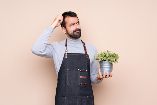 Homme tenant une plante ayant des doutes tout en grattant la tête