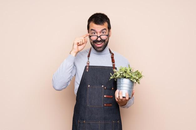 Homme tenant une plante avec des lunettes et surpris