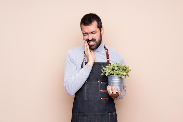 Homme tenant une plante avec des maux de dents