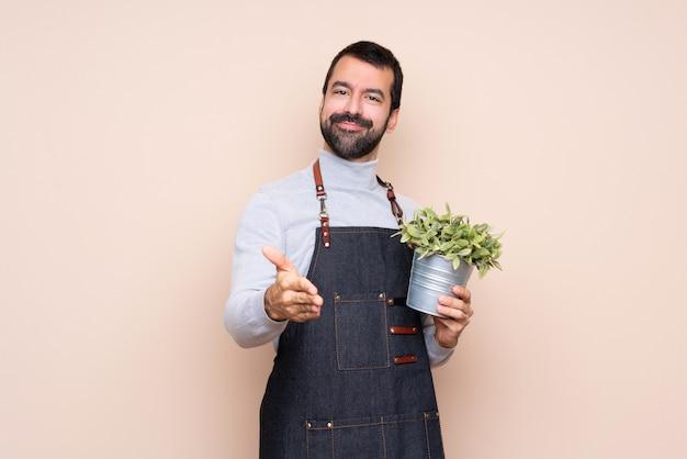 Homme tenant une plante se serrant la main pour conclure une bonne affaire