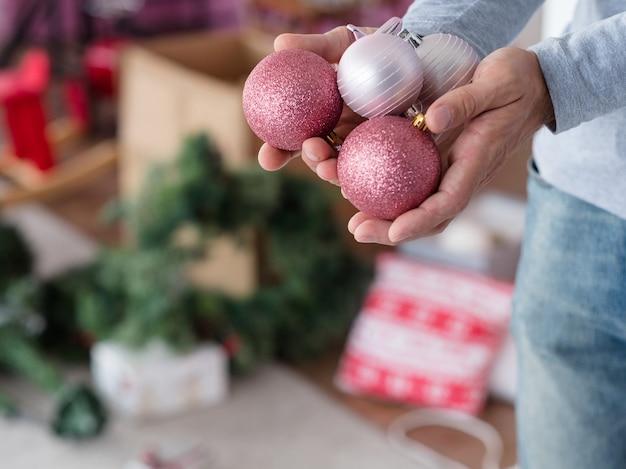 Homme tenant une poignée de boules scintillantes en or rose et argent.