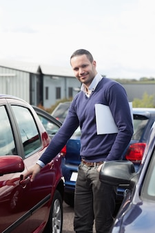 Homme tenant une poignée de voiture en tenant un dossier