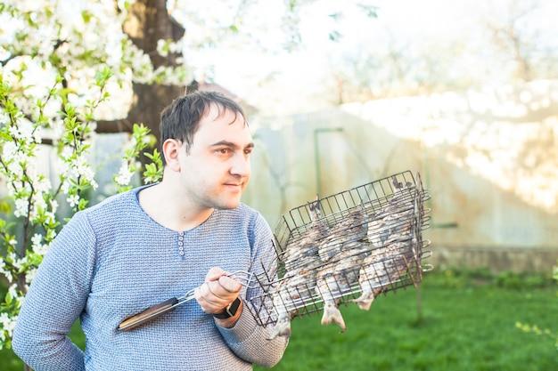 Homme tenant un poisson grillé dans une grille en acier