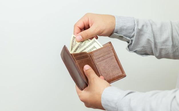 Homme tenant un portefeuille en cuir ouvert plein d'argent ou de dollars en papier
