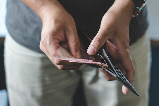 Homme tenant le portefeuille avec plein d'argent.