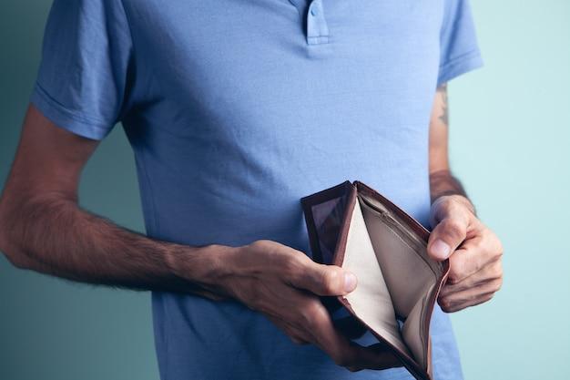 Un homme tenant un portefeuille vide