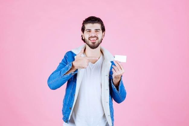 Homme tenant et présentant sa nouvelle carte de visite