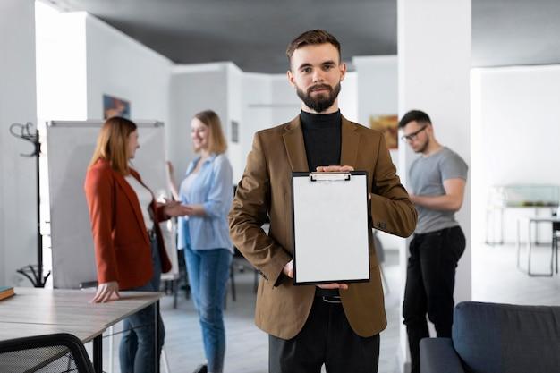 Homme tenant un presse-papiers au travail