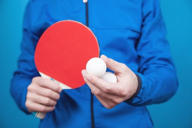 Homme tenant une raquette de tennis et une balle en plastique blanche sur bleu