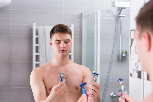 Homme tenant des rasoirs et choisit le meilleur tout en se tenant devant le miroir dans la salle de bain carrelée moderne à la maison