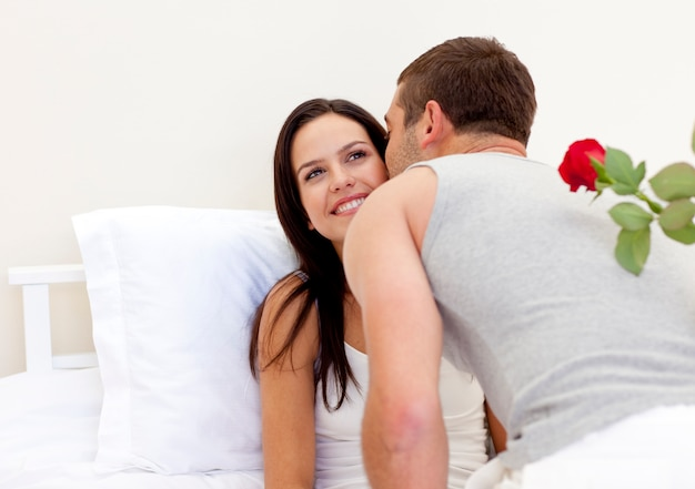 Homme tenant une rose donnant un baiser à sa belle femme