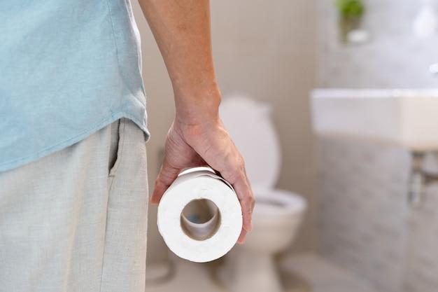 Homme tenant un rouleau de mouchoir devant les toilettes. l'homme a des douleurs à l'estomac, la diarrhée.