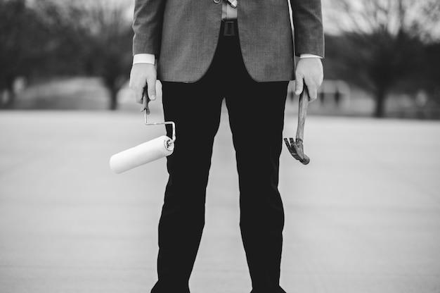 Homme tenant un rouleau de peinture et un marteau