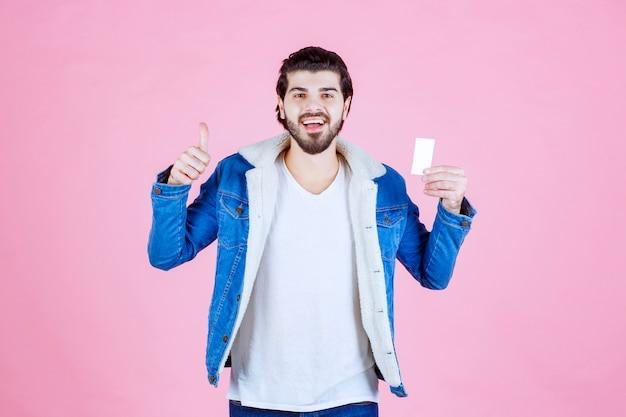Homme tenant sa carte de visite et montrant le pouce vers le haut