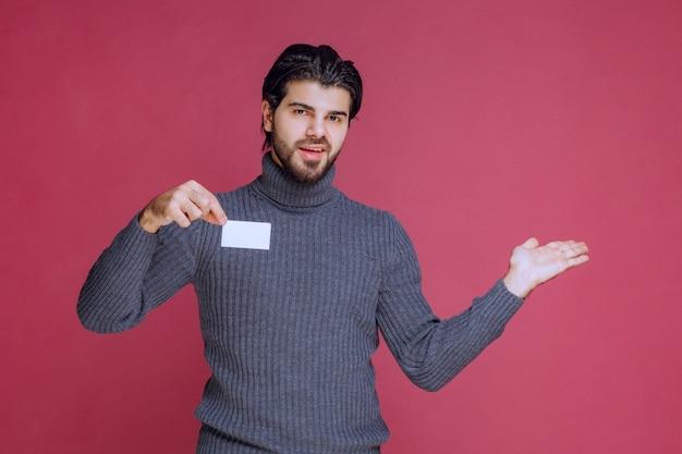 Homme tenant sa carte de visite et pointant vers quelqu'un d'autre.
