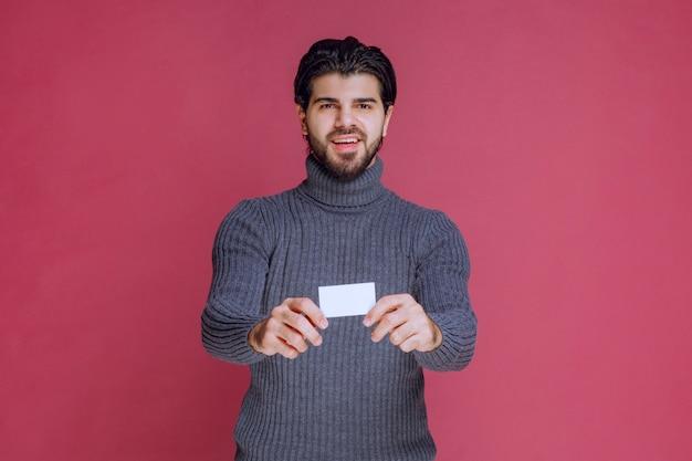 Homme tenant sa carte de visite, la présentant ou la recevant.