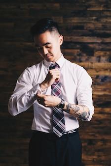 Homme tenant sa manche et sa cravate