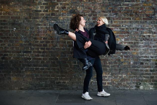 Homme tenant sa petite amie dans ses bras devant un mur de briques typique de londres