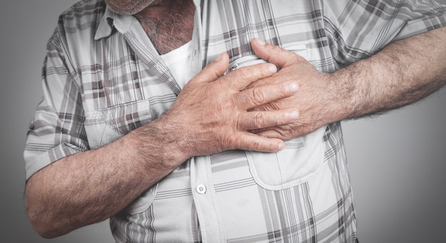 Homme tenant sa poitrine souffrant d'une crise cardiaque.