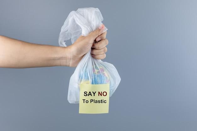 Homme tenant un sac en plastique et un globe à l'intérieur avec un espace de copie pour le texte. protection de l'environnement, zéro déchet, réutilisable, ne dites pas de plastique, concept de la journée mondiale de l'environnement et du jour de la terre