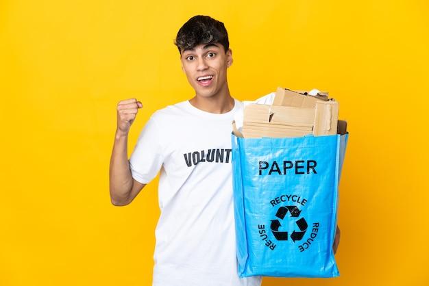 Homme tenant un sac de recyclage plein de papier à recycler sur fond jaune isolé célébrant une victoire en position de vainqueur