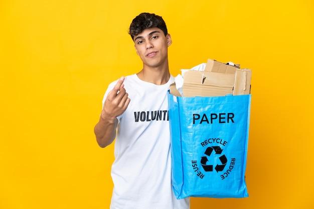 Homme tenant un sac de recyclage plein de papier à recycler sur fond jaune isolé faisant le geste à venir