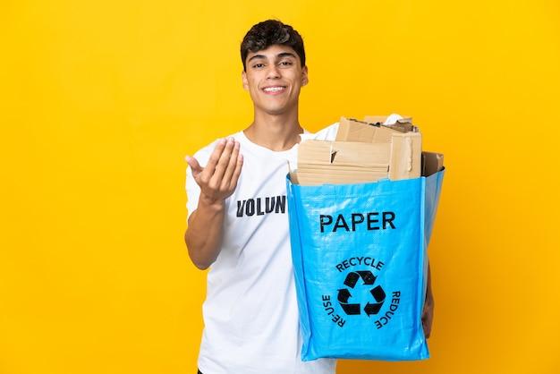 Homme tenant un sac de recyclage plein de papier à recycler sur fond jaune isolé invitant à venir avec la main. heureux que tu sois venu