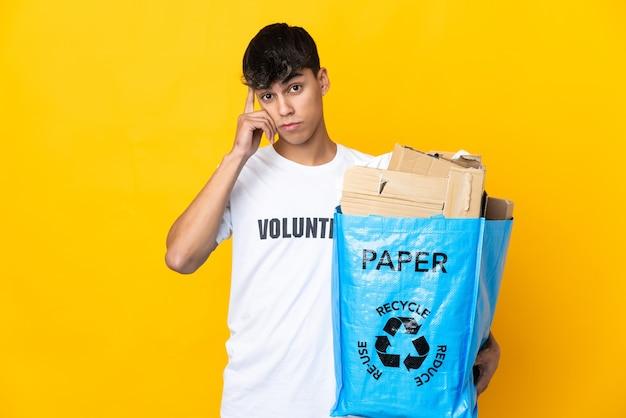 Homme tenant un sac de recyclage plein de papier à recycler sur fond jaune isolé pensant une idée