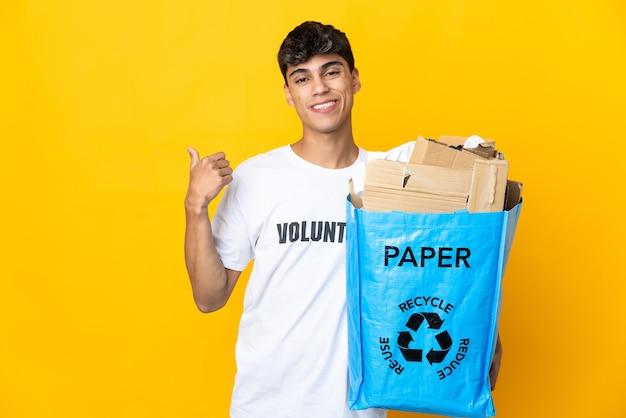 Homme tenant un sac de recyclage plein de papier à recycler sur fond jaune isolé pointant vers le côté pour présenter un produit