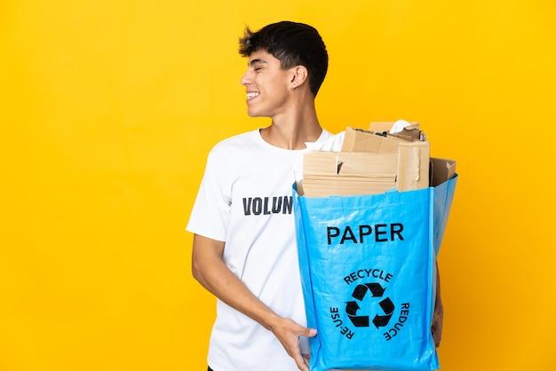 Homme tenant un sac de recyclage plein de papier à recycler sur fond jaune isolé en riant en position latérale