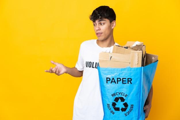 Homme tenant un sac de recyclage plein de papier à recycler sur jaune isolé avec une expression de surprise tout en regardant côté