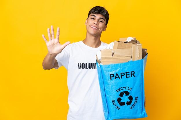 Homme tenant un sac de recyclage plein de papier à recycler sur mur jaune isolé comptant cinq avec les doigts